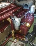 Nu sitter första cylinderlocket på plats, och så även vattenpumpen. Många rör blir det.