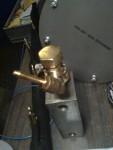 … På en järnbit på den av en massa grejor belamrade arbetsbänken, ligger en liten pryl som ska sitta i änden av oljematarröret. I den sitter några pillimojer. En elementavluftningsventil med vilken man kan kolla när systemet fyllts upp vid fyllning av rörsystemet efter att allt varit tömt. Där sitter oljetrycksgivaren (inte med i bild) samt en böj med en slangnippel. Därifrån ska det gå en slang upp till torpedväggen, där det så småningom skall sitta en mässingmanometer.